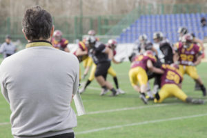 A football coach watches players in action